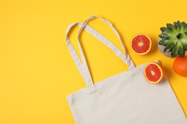 Эко сумка, сочное растение и апельсин на цветном фоне