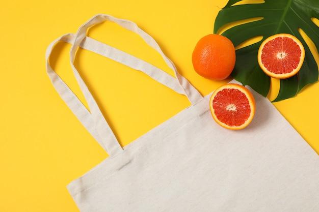 Эко сумка, пальмовый лист и апельсин на цветном фоне
