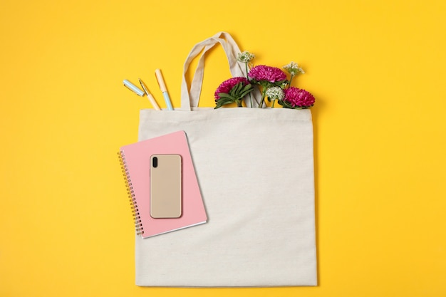Эко сумка, телефон, лук и хризантема на цветном фоне