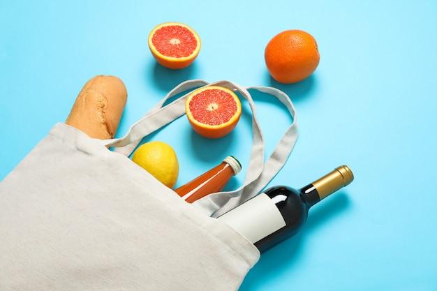 Эко сумка с бутылкой вина, сока, фруктов и багета на цветном фоне