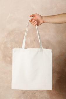 Мужской рукой, держащей сумку коричневый фон