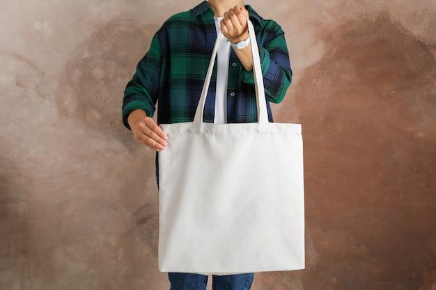 Молодая женщина, держащая сумка против коричневого фона