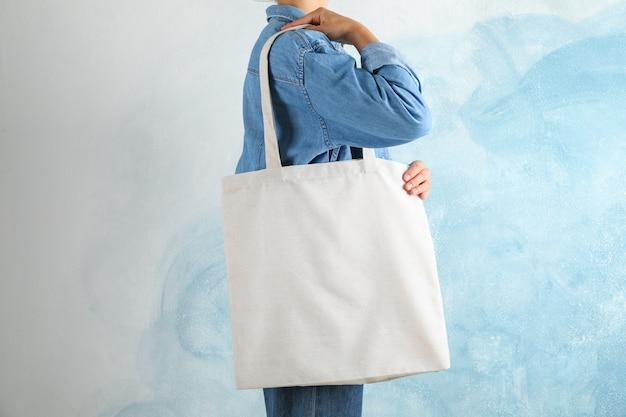 Молодая женщина, держащая сумка на синем фоне