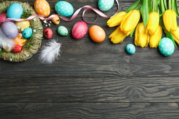 Гнездо с красочными пасхальными яйцами, цветами и перьями на деревянном фоне