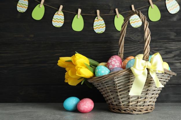 Пасхальная корзинка с красочными яйцами и цветами на деревянном фоне