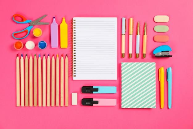 Плоская композиция с канцелярскими принадлежностями на розовом столе