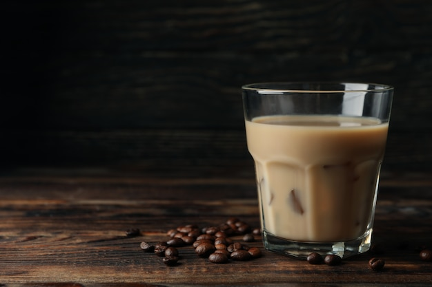 木製の背景にアイスコーヒーのグラス。コーヒーの種