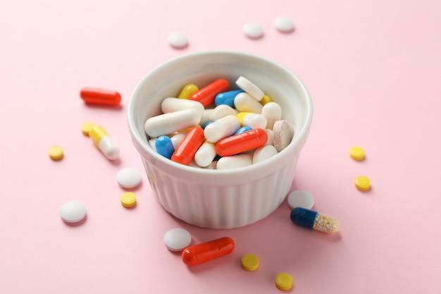 白いボウルとピンクのテーブルに別の薬をクローズアップ
