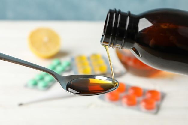 錠剤に対してスプーンに注ぐシロップ、クローズアップ