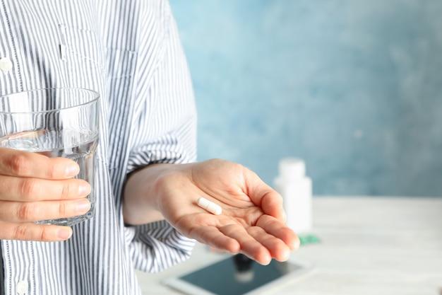 女性は錠剤と水のガラスを保持します