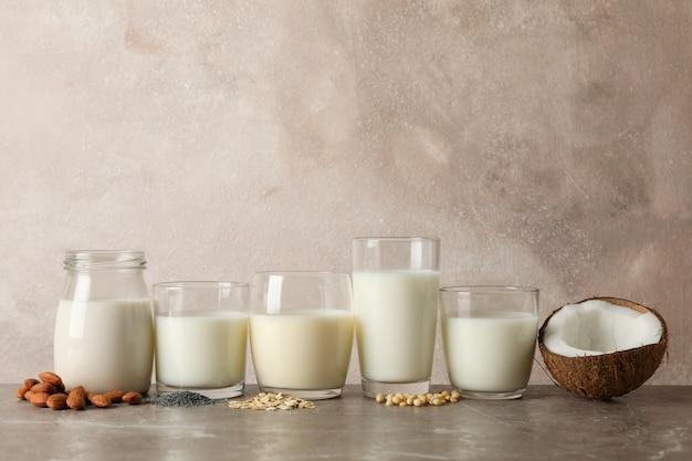 茶色のテーブルにさまざまな種類のミルクのグラス