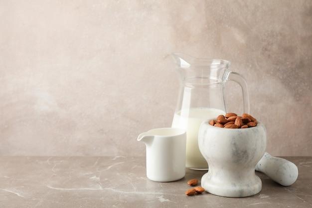 アーモンドミルクの水差し、茶色のテーブルにアーモンドの種子とモルタル