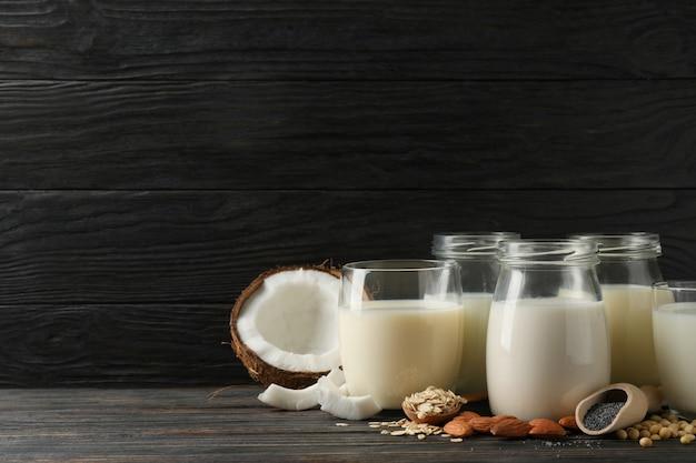 木製のテーブルにさまざまな種類の牛乳とメガネ