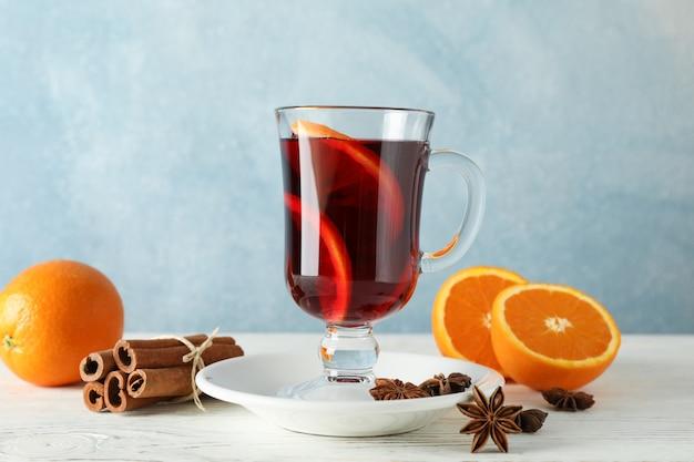 グリューワイン、オレンジ、シナモンの白い木製のテーブル
