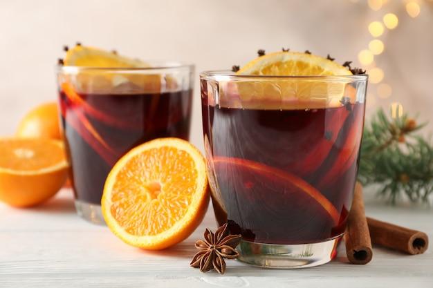 白い木製のテーブルにオレンジとおいしいグリューワインのグラス
