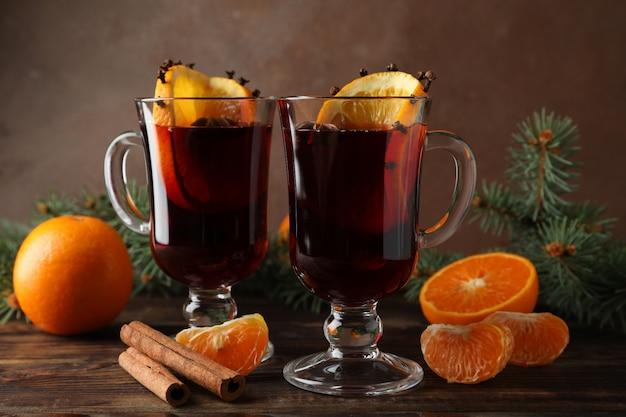 木製のテーブルにオレンジとおいしいグリューワインのグラス