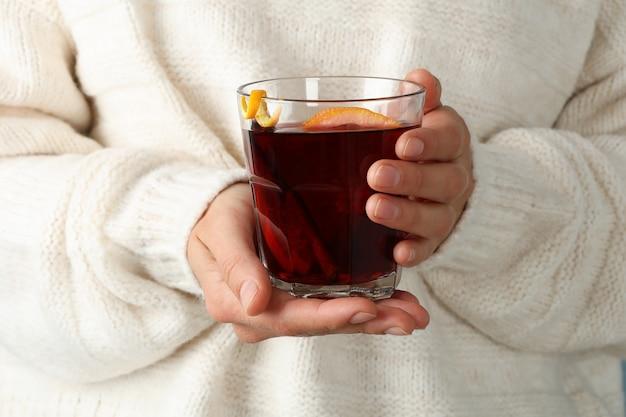 Девушка в свитере держит стакан с глинтвейном, крупным планом