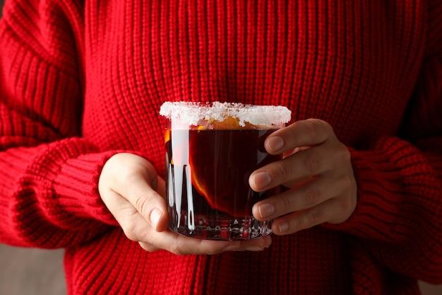 グリューワインとガラスを保持している赤いセーターの女の子をクローズアップ