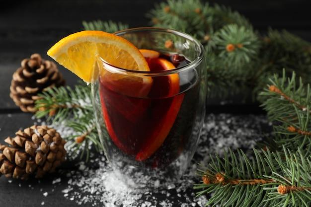 装飾された木製のテーブルにオレンジとおいしいグリューワインのグラスをクローズアップ