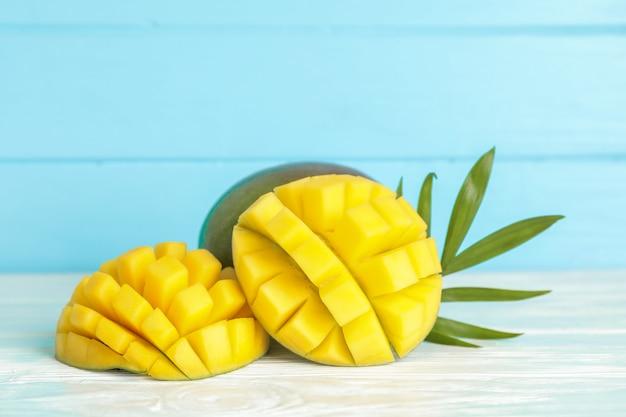 Вырезать спелых манго и пальмовых листьев на белом столе
