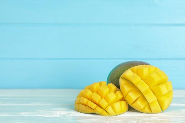 Вырезать спелых манго на белом столе