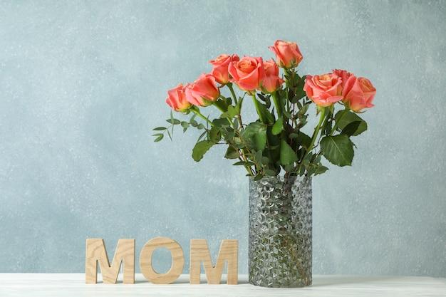 オレンジ色のバラと白いテーブルに碑文ママの花瓶