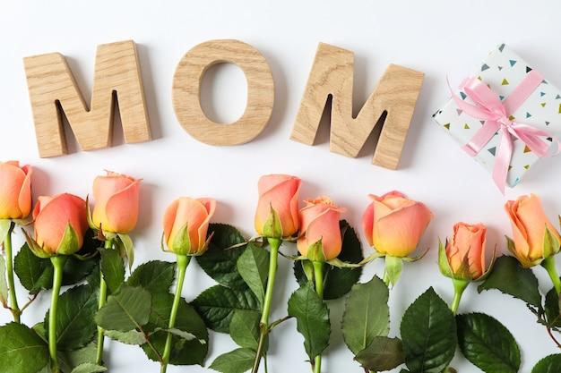 Надпись мама с розовыми розами и подарком на двухцветном столе, вид сверху