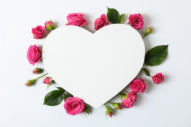 美しいピンクのバラとハートの形をした空白のグリーティングカード
