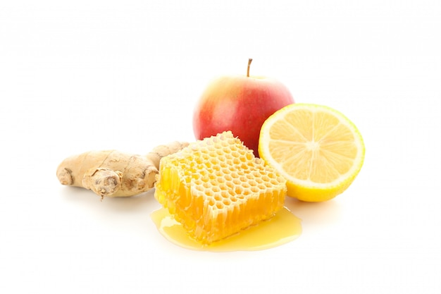 Соты, яблоко, лимон и имбирь на белом фоне