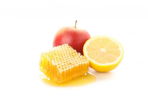 Соты, яблоко и лимон на белом фоне