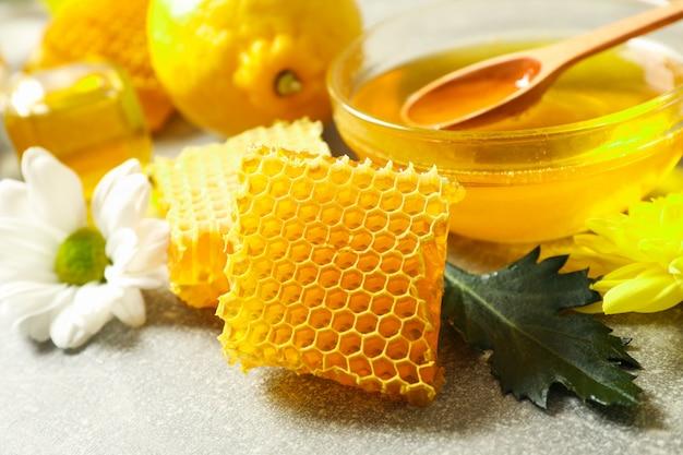 Соты, лимон и цветы на сером
