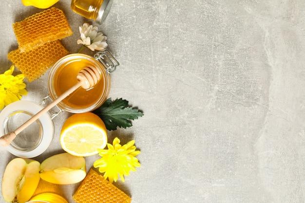 Плоская планировка с медом, цветами и фруктами на сером