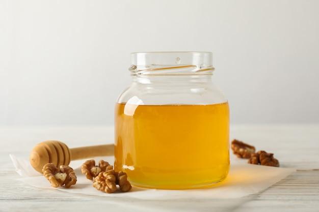 クルミ、ひしゃく、羊皮紙、白い背景の上に蜂蜜が付いているガラス瓶