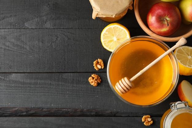 蜂蜜、ひしゃく、クルミ、木製の背景、上面に果物