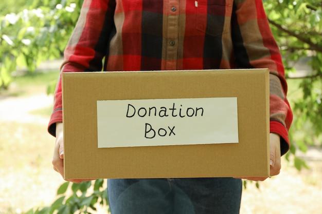 屋外の寄付の紙袋を保持している女性。ボランティア