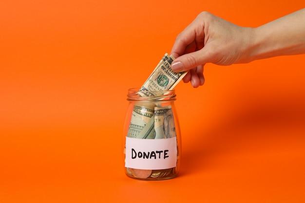 女性の手がオレンジ色のスペースのガラスの瓶にお金を置く