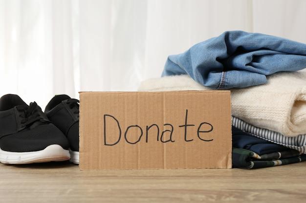 Текст пожертвовать и одежду на деревянном пространстве. концепция пожертвования
