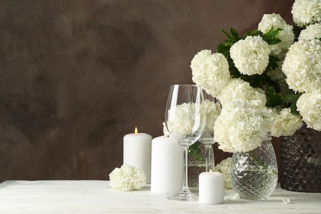 アジサイの花と茶色の空間に対するキャンドルのコンポジション。ロマンチックな夜