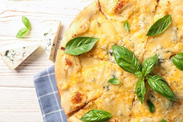 チーズの部分と白い背景の上のバジルのピザ