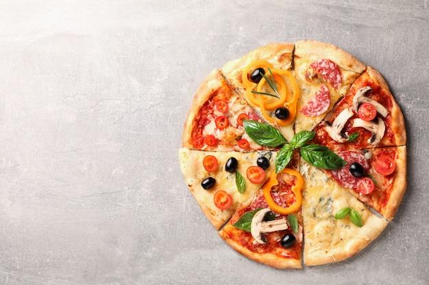 灰色の背景上の別の部分でおいしいピザ