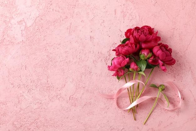 美しい牡丹と色の背景にピンクのリボンの花束