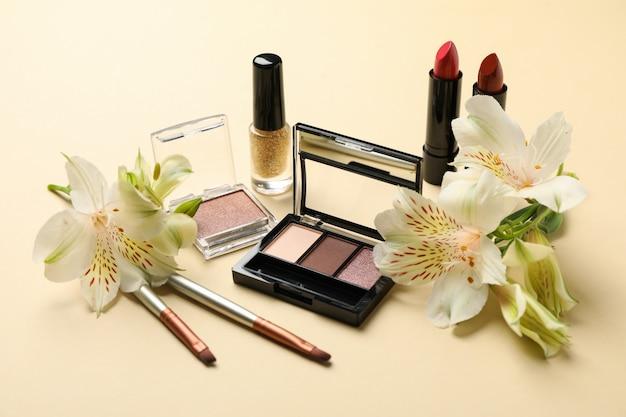 Разная косметика для макияжа и цветы на бежевом фоне