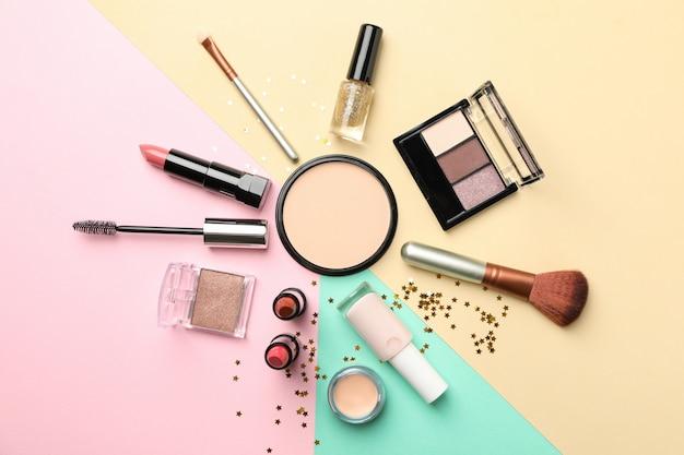 Разная косметика для макияжа на цветном фоне