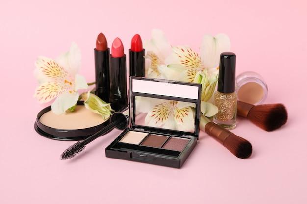 Разная косметика для макияжа и цветы на розовом фоне