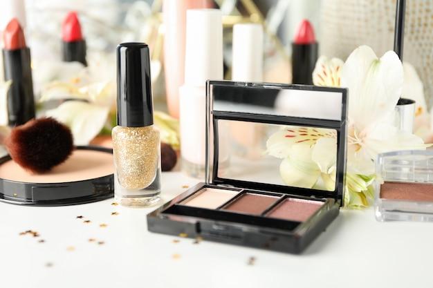 Различная косметика для макияжа и цветы на белом фоне