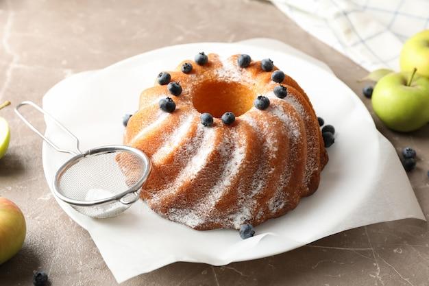 Торт с сахарной пудрой и черникой на столе