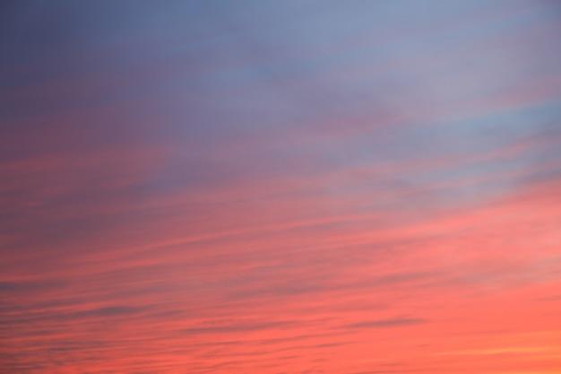 燃えるような雲、黄色、オレンジ、ピンク色、自然の背景と劇的な夕焼け空の背景。美しい空