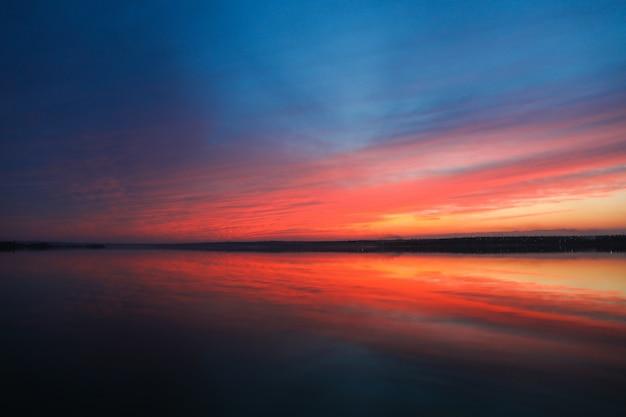 劇的な夕焼け空の背景に川、燃えるような雲、黄色、オレンジ、ピンク色、自然の背景。美しい空