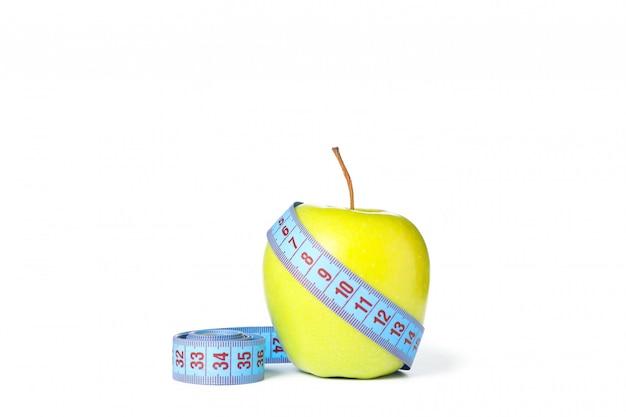 Измерительная лента и яблоко, изолированные на белом