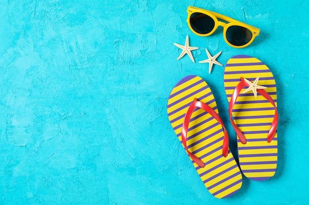 Шлепанцы, солнцезащитные очки и морские звезды на цвет фона, место для текста и вид сверху. концепция летних каникул